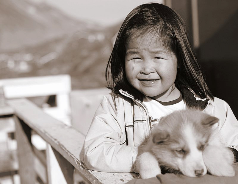 Black and white photograph of a young Inuit child with husky puppy. Photo credits to: Nick Russill