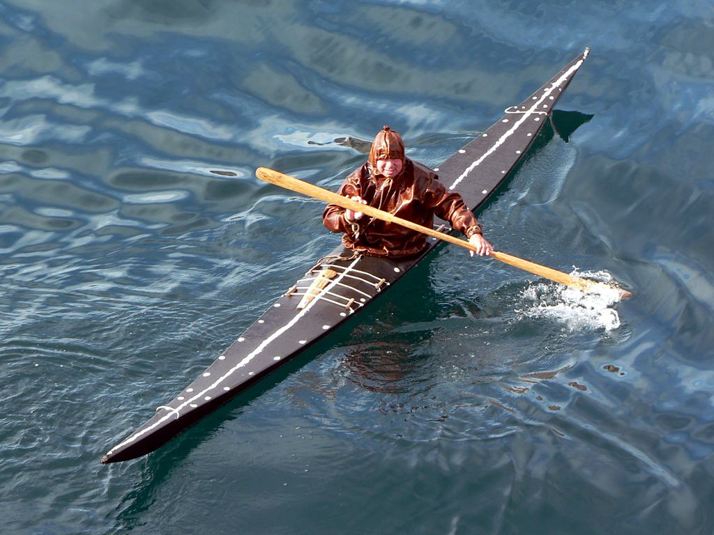 Inuit kayaker in a kayak and clothing made of seal skins.