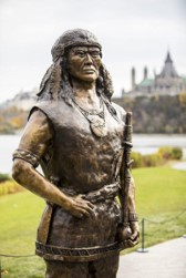 Statue of Tessouat, Algonquin Chief who controlled trade along the Ottawa River in the first half of the 17th century and who denied Champlain passage further west. Parliament buildings in the background. Credits to: Canadian Heritage