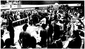 Representatives arriving and standing around long tables. 7th Annual General Assembly of Union of BC Indian Chiefs, April 1975. Source: Union of BC Indian Chief/ Library and Archives