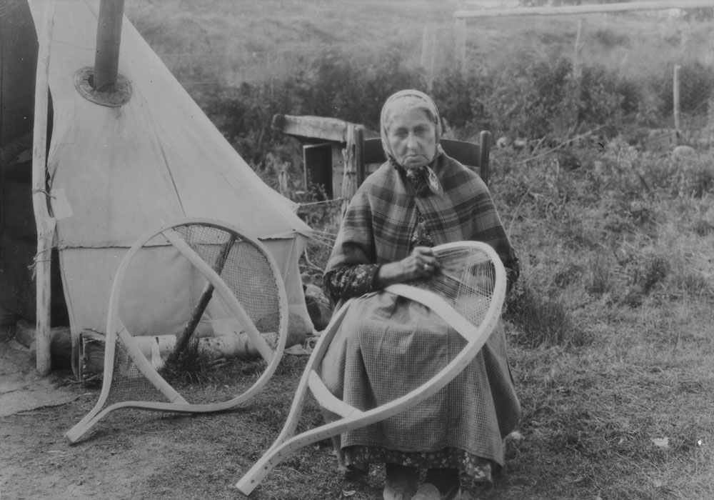 Indigenous woman, possibly Innu, making snowshoes.