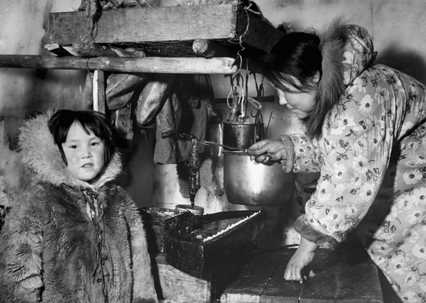 Inuit woman [and young girl, Marion Bolt (Hayohok)] tending the seal-oil inside an igloo in Western Arctic, N.W.T. [Nunavut], 1949  Photo credits to: Richard Harrington / Canada. Dept. of Indian and Northern Affairs / Library and Archives Canada / PA-143237 (Open Access 90) MIKAN No. 3202745 (Access 90 Open) [42]