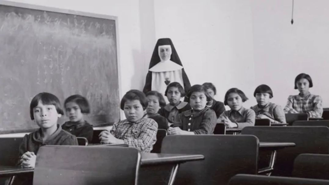 Group of female students [7th from left Josephine Gillis (nee Hamilton), 8th from left Eleanor Halcrow (nee Ross)] and a nun (Sister Antoine) in a classroom at Cross Lake Indian Residential School, Cross Lake, Manitoba, February 1940. Credits to: Canada Dept. Indian and Northern Affairs/ Reuters / Library and Archives Canada