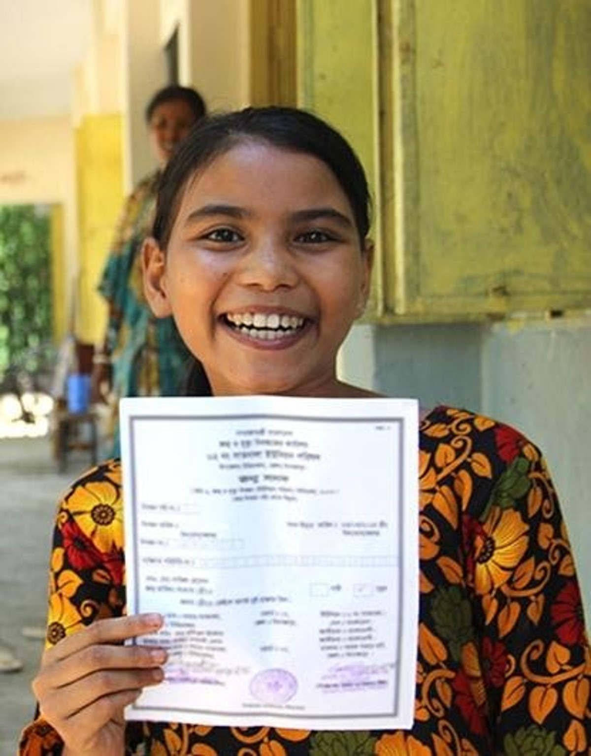 A girl smiles after receiving her birth certificate in a program run by Plan International. Note: all infants born in Canada receive birth certificates. Credits to: Plan International [149]