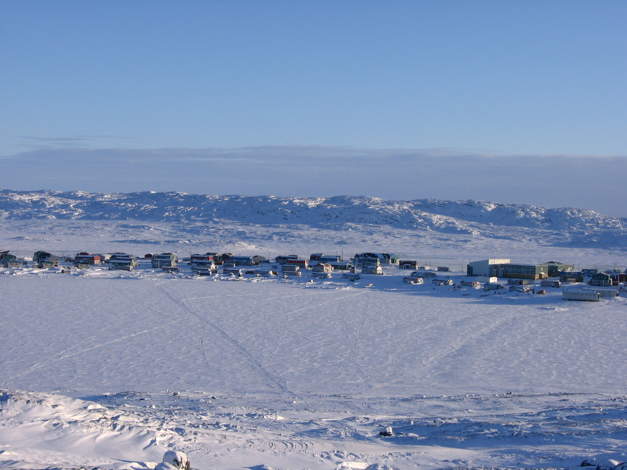Town on a snowy plain with mountains in the background. Kangiqsualujjuaq, Nunavik. Photo credits to: Richard Wetzel.