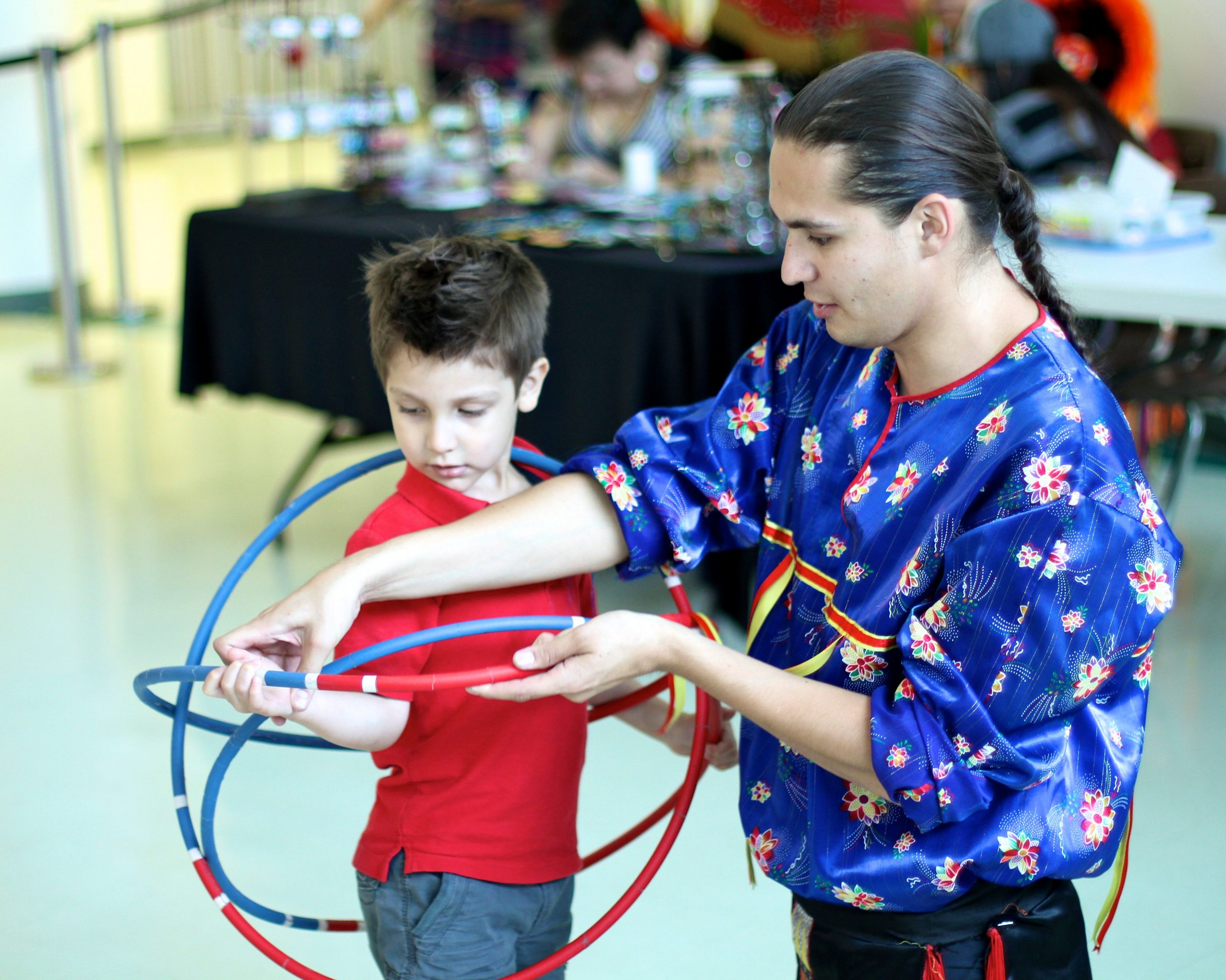 "Hoop dancer teaching young boy. ""Mosaic Regina - First Nations Pavillion"", FNUC Photo by: Alec Couros (CC BY-NC-SA 2.0) [184]"