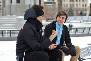 two people seated on a bench having a conversation