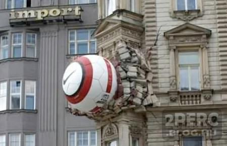 photo of a large soccer ball embedded in the side of a building