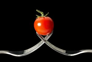 image of a small tomato held up by two forks