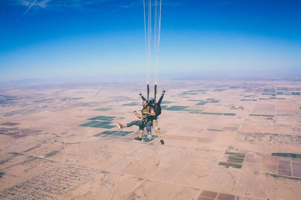 photo of two skydivers connected to each other as they parachute downward