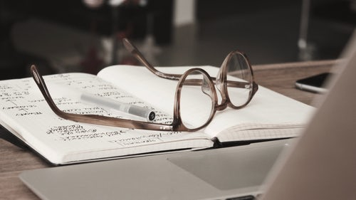 photo of a pair of glasses resting on a notebook