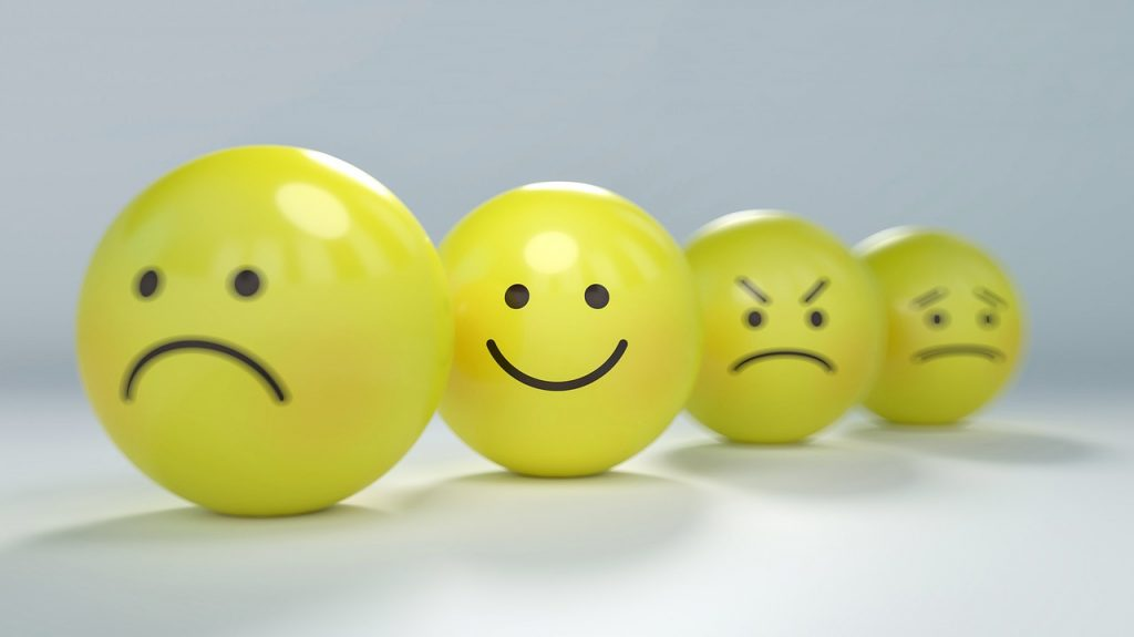 photo of a series of yellow balls with sad, happy, and other emotional faces