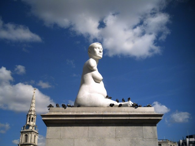 Figure 1-10. A photograph of the white marble sculpture of Alison Lapper. She sits atop a large stone plinth, naked, with her breasts and belly, at seven months pregnant, displayed. Her shortened right leg is outstretched, and her right arm seems to end just below the head of the humerus. The photo is set against a blue sky, with the head of the short-haired figure gazing out the right of the frame, into the sun.