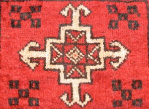 Figure 1-2 shows a red woven rug with patterns in black and white. At the center of the rug is a diamond, which is encased in a square. The square sits centrally in a larger cross/plus sign. An arrow-like form extends from the end of each arm of the cross.
