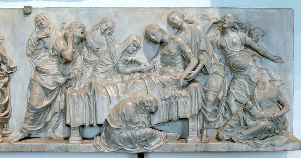 Figure 1-6. A marble relief depicts a women half lying in bed, half being supported by two female attendants. One female attendant holds a baby near the head of the bed, while five other attendants wail in despair around the bed.