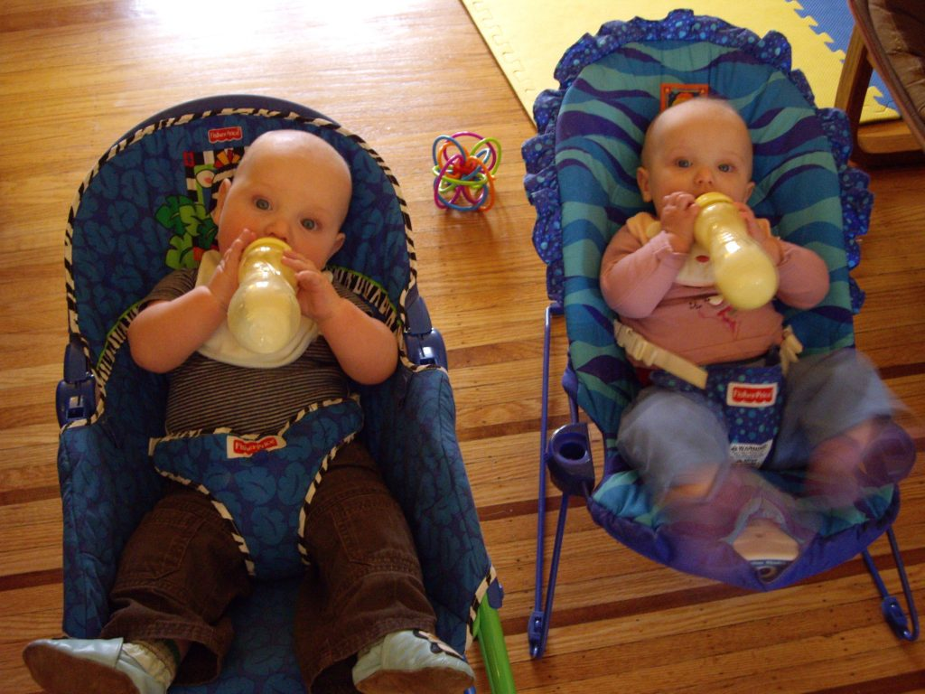 Babies drinking from milk bottles