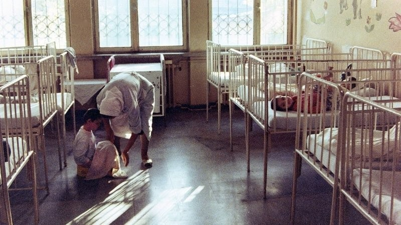 An image taken from an institute in Romania in 1992. A caregiver is bent over a child who is sitting on the floor. They are in a walkway between rows of cribs, some of which have children in them. There are large windows in the room, and what appear to be pictures of flowers on the walls that the cribs are up against.