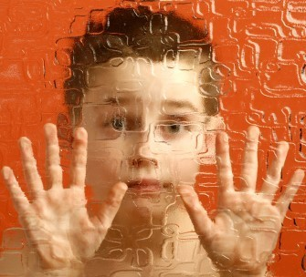 An image of a child in front of an orange background. The child has their hands up on a plastic wall. The wall is infront of the child, and is blurring the view of the child.