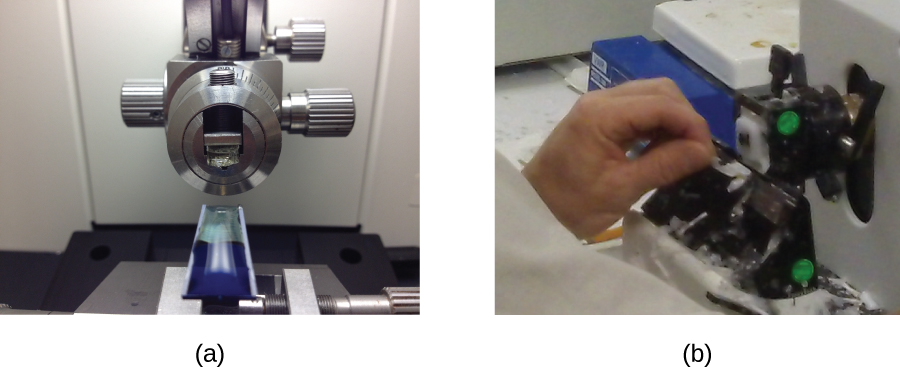 Photograph a shows a blue solid specimen sits below a mechanical dial. Photograph b shows a person holding a dial on a machine.