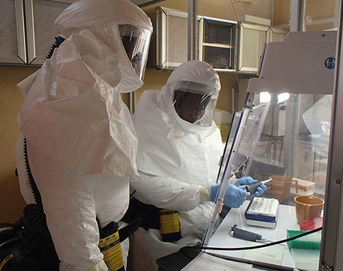 A photograph of two individuals in white biohazard suits that completely covers the individual, complete with head and face covering. They are working in a hood.