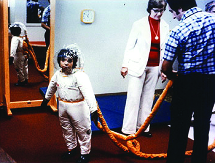 Photo of a boy in a suit similar to a space suit.