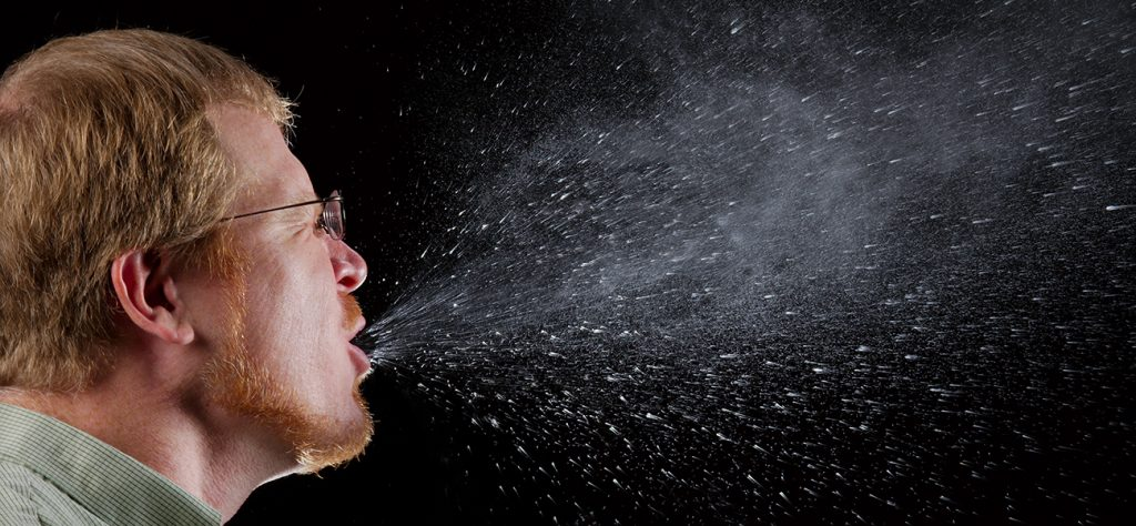 Person sneezing; the sneeze spray is shown.