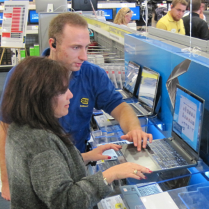 A 20-30 year old blonde man assisting a 40-50 year old brunette woman in front of a laptop.