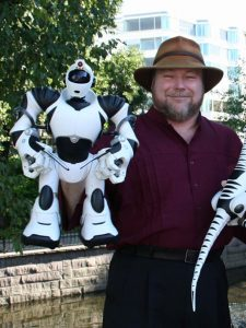 35-45 year old man in a Tilley hat standing by a wall and holding his robot creation (approximately 14 inches tall)
