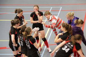 Women's volleyball team on a time out being instructed by their coach