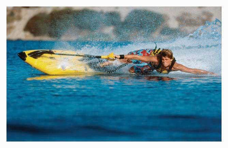 Rider on a yellow board appearing to be skimming the water i.e. parallel to the water.