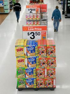 "Four columns and four rows of cereal boxes stacked at the end of a supermarket's aisle with a large ""low price"" sign across the top."