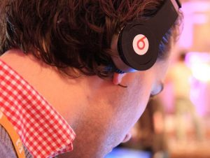 Side profile picture of a young man wearing Beats headphones