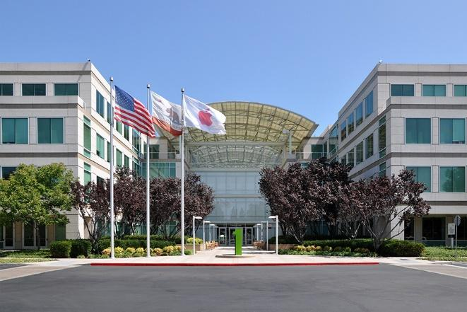 Photograph of Apple Inc.'s headquarter buildings in Cupertino, California. Two squarish buildings with an arched-roof in between. The United States, California and Apple flags are flying in the open-air entrance.