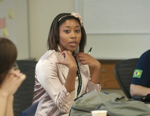 Woman sitting at the table speaking out in class.