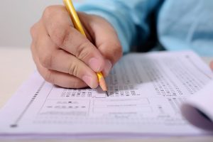 Selective focus of a hand with a pencil writing on a test paper.