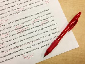 Overview shot of a page of writing with corrections in red pen.