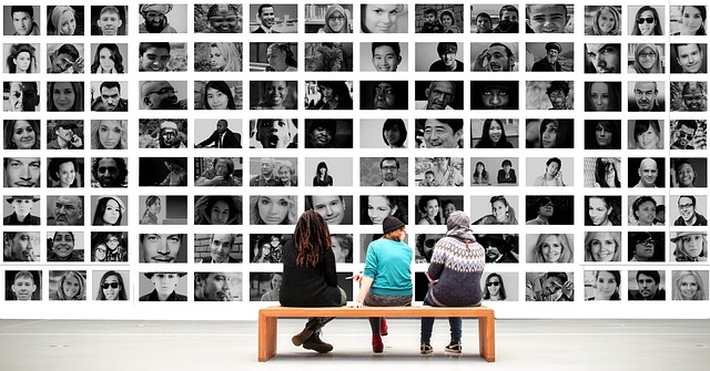 Three people sitting on a bench before a wall of photographs.