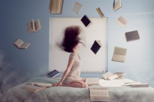 Woman sitting on a bed with books flying in the air.