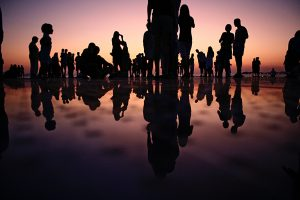 Silhouette of people standing on mirror during golden hour.