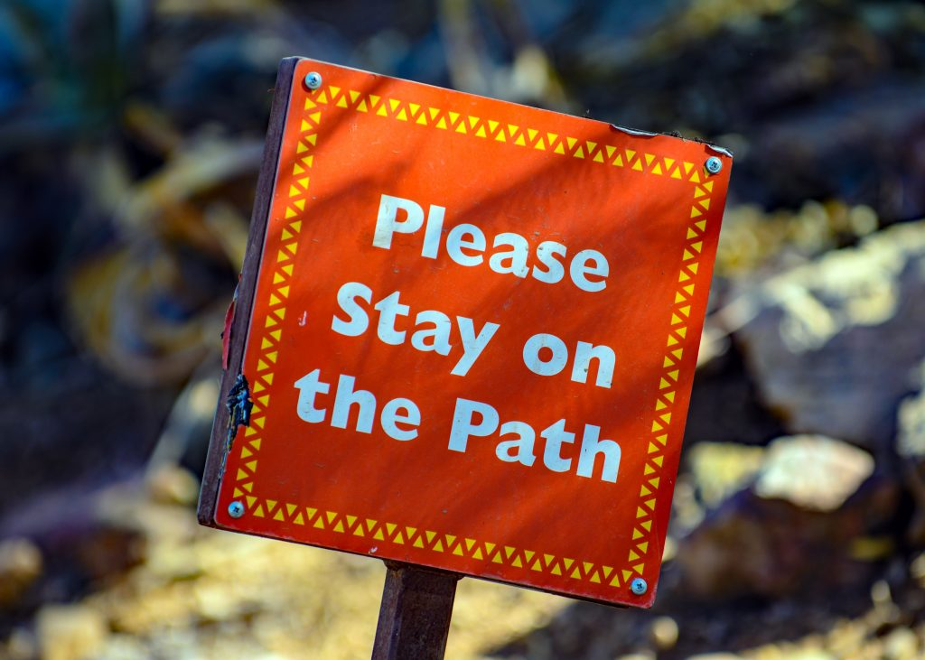 Please stay on the path sign.