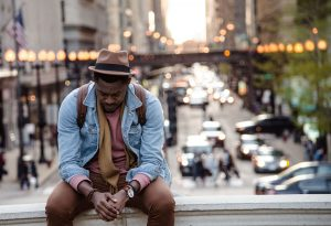 Man sitting on edge of bridge in a city.