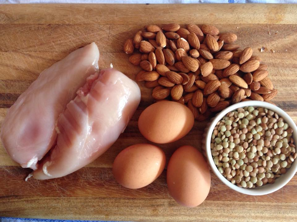 Chicken, eggs, and nuts on a carving board