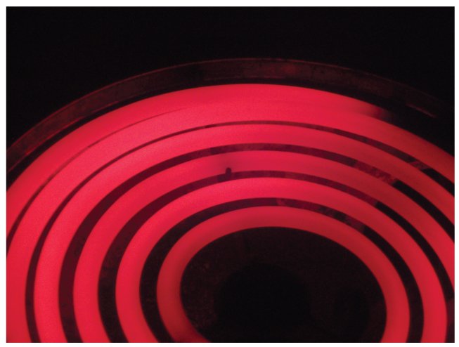 This photo shows a red hot electric stove top.