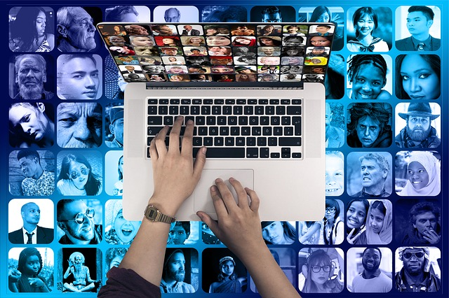 Two hands typing on a laptop seen from above. A collage of many faces fill the background.