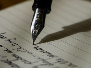 A pen writing on lined paper