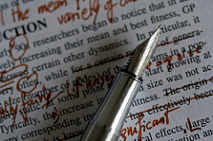 A pen poised on top of typed page that contains many corrections in red ink