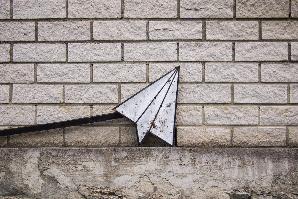 Paper airplane against a brick wall.