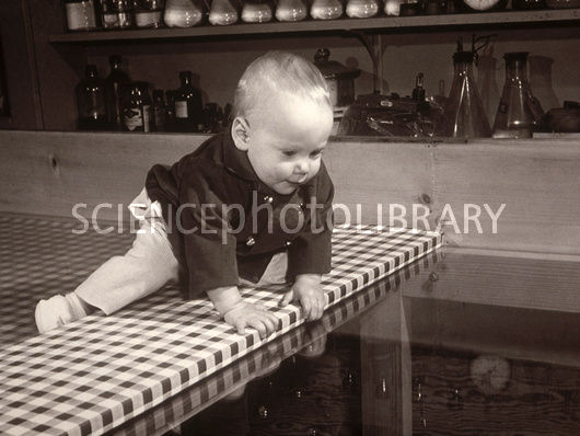 black and white photo of baby approaching the edge of a table