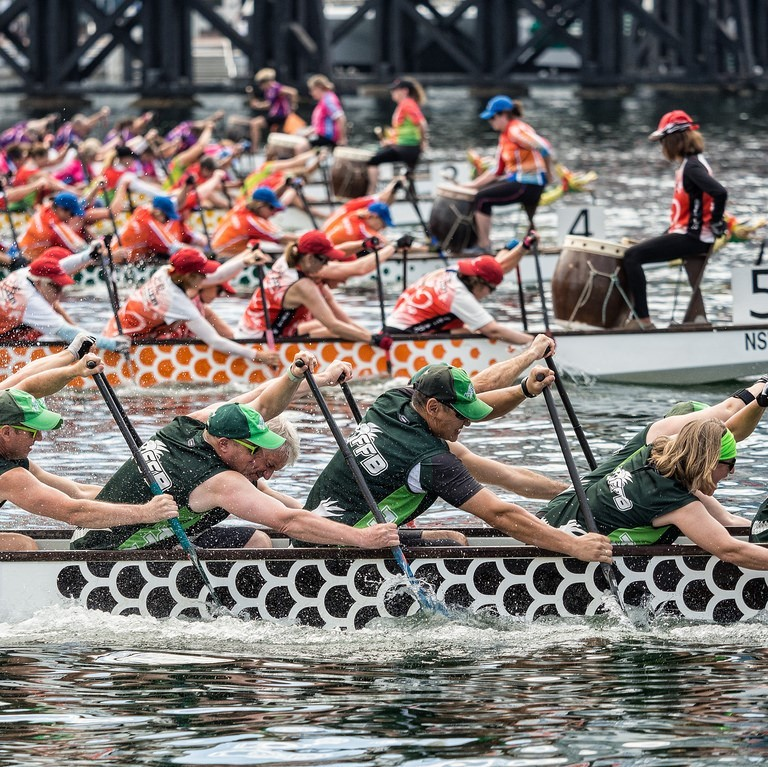 Boats filled with teams of rowers compete in a race.