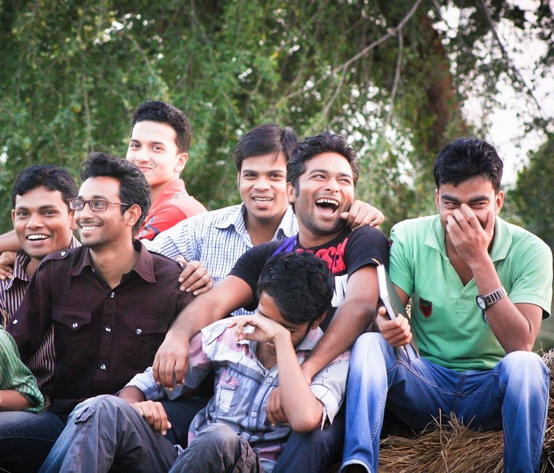 A group of young men sit together laughing and smiling